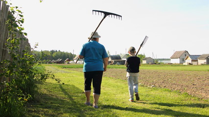 An elderly woman farmer and a little boy in a cap and t-shirt go with a rake in the country yard on a Sunny summer day - child labor, outdoor recreation