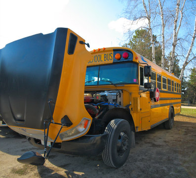 Yellow Orange School Bus in parking lot with hood open for service repair is backlit on a sunny day.