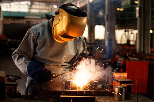 Industrial welder is welding metal part in the factory.