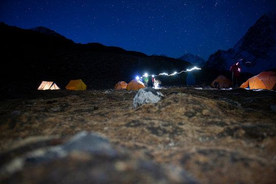 Langzeitbelichtung von Bergsteigern mit Stirnlampen im Basislager in der Nacht unter Sternenhimmel