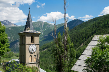 CLOSE UP: Old church tower decays in the vibrant green mountains in France.