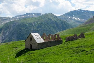 Old medieval country house decays in the middle of a vibrant green meadow.