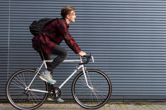young stylish guy rides a white bicycle on a gray striped wall, student travels to school