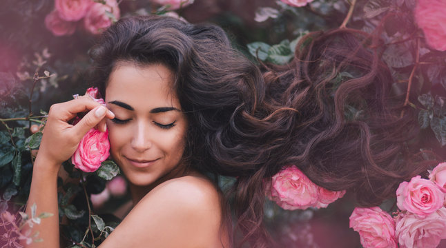 Beautiful young woman with long curly hair and perfect skin. posing near roses in a garden. Nude make up. Close up portrait