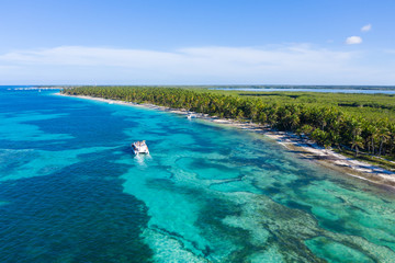 Fototapete - Aerial view from drone on tropical beach with palm trees and speed boats in caribbean sea