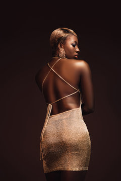 rear view of fashionable african american woman with short hair isolated on brown