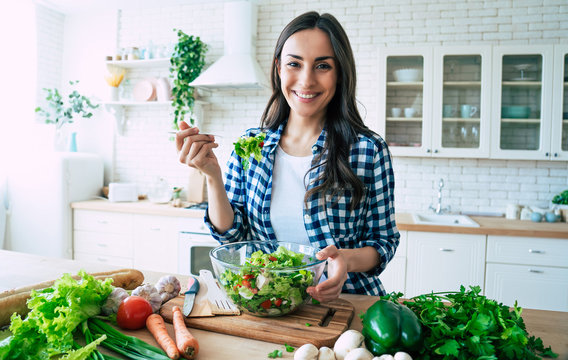 Healthy lifestyle. Good life. Organic food. Vegetables. Close up portrait of happy cute beautiful young woman while she try tasty vegan salad in the kitchen at home.