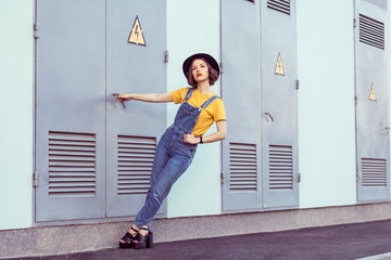 young woman in blue denim overalls and yellow tshirt with black hat sensual looking up while posing near industrial building . outdoor shot in the summertime