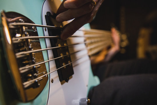 Closeup on the bass guitar strings, while someone is playing