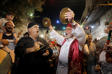 Palestinian musicians perform to celebrate the breaking of the fast during Ramadan, the Muslim holy month, in the walled Old City of East Jerusalem