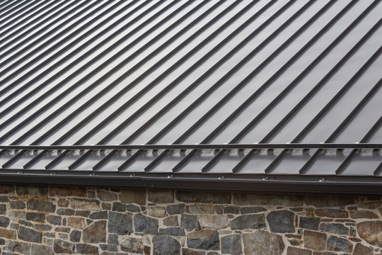 Standing seam modern metal roof over vintage stone wall, horizontal aspect