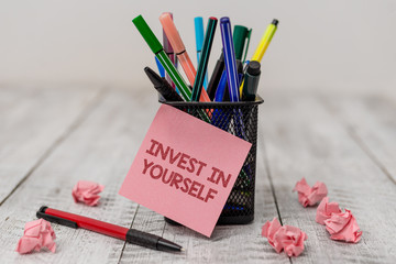 Conceptual hand writing showing Invest In Yourself. Concept meaning learn new things or materials thus making your lot better Writing equipment and paper scrap with blank sheets on wooden desk