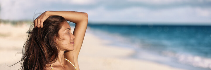 Wall Mural - Banner woman relaxing touching her hair wellness summer holiday ocean beach panoramic background on tropical Caribbean summer vacation panorama. Asian girl breathing clean air.