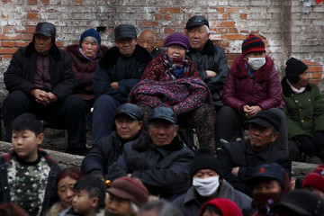 Locals and retired workers watch a Chinese opera performance that Xinyuan Steel put on in Anyang
