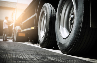 Semi truck trailer parked at the warehouse.  Close-up a big truck wheels and tires. Industry cargo freight truck transportation.