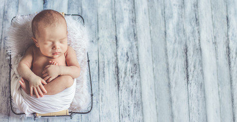 Adorable newborn baby sleeping in cozy room. Cute happy infant baby portrait with sleepy face in bed. Soft focus at the baby eyes. Newborn nursery care concept.