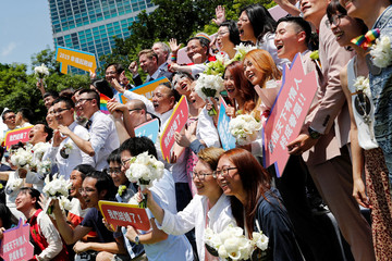 Gay and lesbian newlyweds pose for group photo at a pro same-sex marriage party after registering their marriages in Taipei