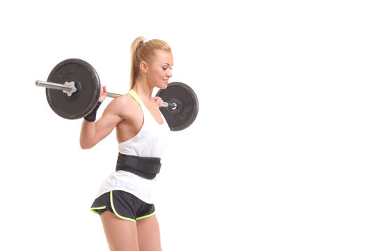 Beautiful fit woman smiling with a barbell