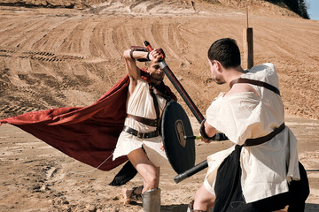 Tuinposter Kamperen A concept photo of a Roman battle of two warriors of the Colosseum in action with aggressive emotions in full military uniform on a desert landscape on a sunny day with a dry sun.