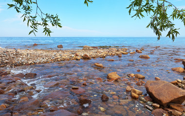 336 rivers flow into the deepest freshwater lake Baikal on the planet. One of the mountain rivers that feed the lake with clean water. Summer lakeside landscape