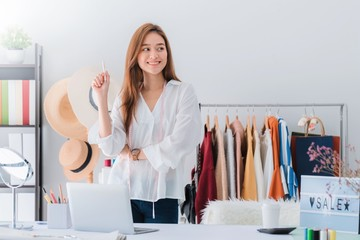 Beautiful asian woman fashion designer standing in the clothing store and studio. In front of the camera to recording vlog video live streaming.Business online influencer on social media concept.