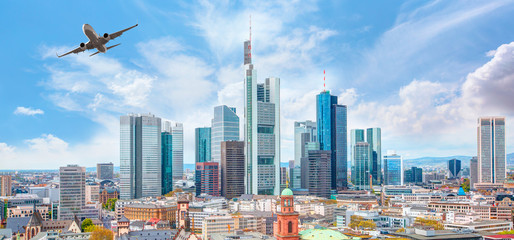 Airplane flying over business skyline of Frankfurt am Main, Germany - financial capital of the european union Wall mural