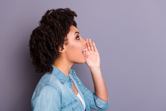 Profile side view of amazed surprised cheerful hipster lady scream shout ads hold hand  share private information wear stylish trendy jeans denim clothing  youth isolated grey background