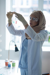 Young female chemist wearing glasses studying chemical liquids