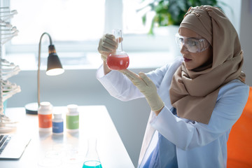 Woman wearing gloves holding chemical glass with pink chemical