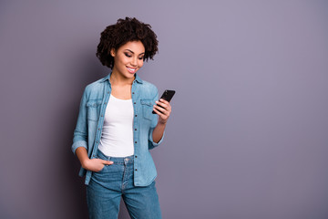 Fototapete - Portrait of pretty attractive blog blogger teen hold hand modern technology look news feed social network account news information read wear fashionable denim outfit isolated grey background