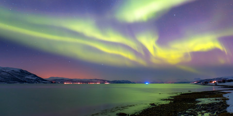 Wall Mural - Snow storm on the empty road - Snow covered road on a winter - Northern lights in the sky over Tromso, Norway