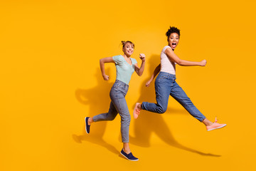 Full length body size view photo cheerful playful youth free time weekend holiday summer active race hurry childish curly haircut stylish trendy t-shirt jeans clothing isolated yellow background Fototapete
