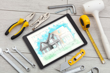 Tablet with construction tools and house plan concept