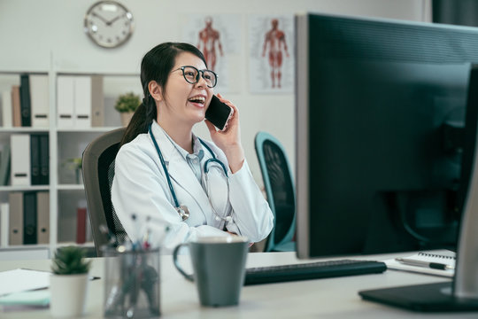 Smiling asian woman doctor talking on mobile phone at hospital. young female medical employee work in clinic office relax chatting on cellphone laughing gossip cheerful. happy lady having fun break
