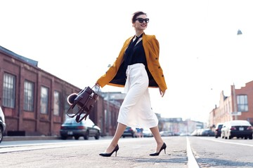 Happy young business woman walking on the street. Wall mural