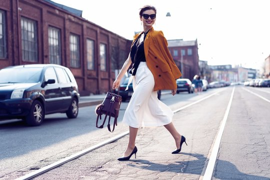 Happy young business woman walking on the street.