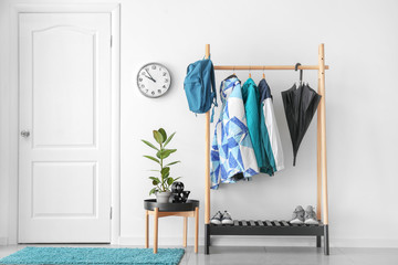 Rack with clothes in stylish interior of hall