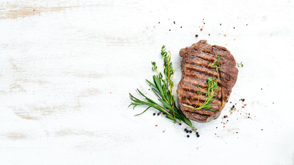 Printed roller blinds Steakhouse Grilled ribeye beef steak, herbs and spices on a white wooden background. Top view. Free space for your text.