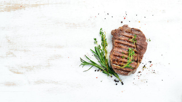 Grilled ribeye beef steak, herbs and spices on a white wooden background. Top view. Free space for your text.