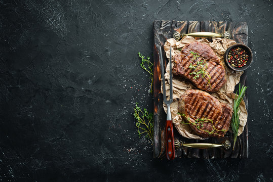 Grilled beef steak medium rare on a black stone table. Top view. Free space for your text.