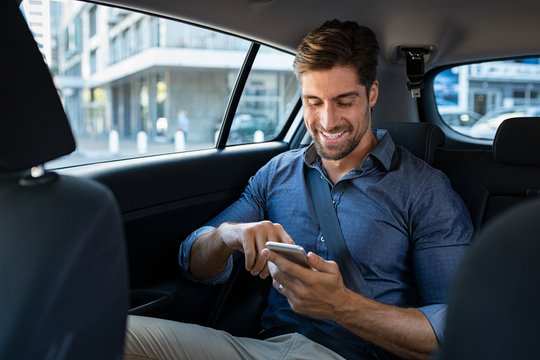 Happy business man in car using phone