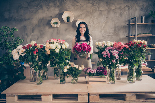 Portrait of her she nice attractive lovely charming cute cheerful cheery wavy-haired lady vendor holding in hands giving bunch greetings congrats birthday concrete wall indoors workplace