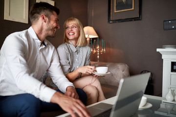 Cheerful partners drink coffee and work at laptop