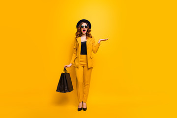 Full length body size photo beautiful crazy she her lady carry open palm clothes packs perfect look new low price sale discount wear specs formal-wear costume suit isolated yellow bright background Wall mural