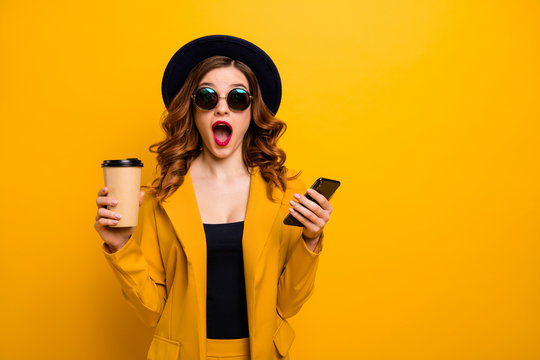 Close up photo beautiful funky she her lady open mouth amazed hands arms telephone vacation traveler hot beverage paper container reader wear specs formal-wear suit isolated yellow bright background