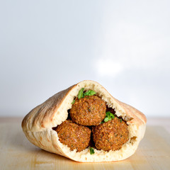 Falafel balls in a pita on wooden table over Israel flag background. Falafel plays an iconic role in Israeli cuisine and is widely considered to be the national dish of the country.