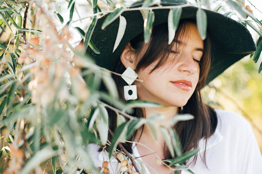 Stylish boho girl in hat and with modern earrings posing among green olive branches in soft evening light. Young fashionable woman relaxing on tropical island. Summer vacation. Space for text