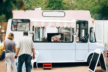 Food truck at summer street food festival in the city. Stylish retro food van truck with desserts, macaroons and ice cream. Summer market in the city. Space for text menu