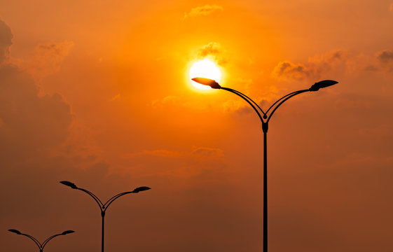 Silhouette street electric pole with beautiful orange and yellow sunset sky and clouds in the evening. Street lamp light. City road lamp post for illumination Power and energy conservation concept.