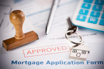 An approved Mortgage loan application form with house key and rubber stamp